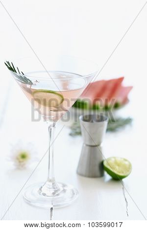 Light pink cocktail mocktail in a martini glass decorated with a slice of lime and garnish with a slice of watermelon and flowers in the background