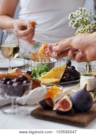 Hands reaching out for snacks at a party, selection of cheese, cured meat, fresh fruit, white wine and flowers