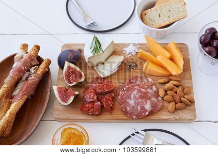 Cheese and cured meat charcuterie selection with fresh fig, rockmelon and almonds