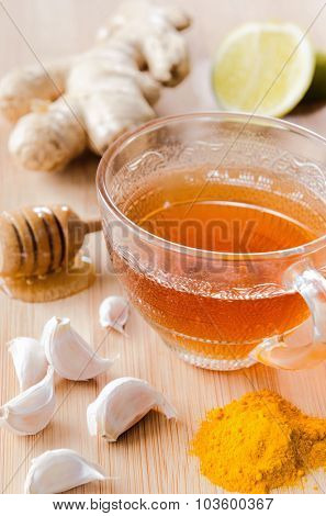 Cup of tea with ginger, lemon, honey, garlic, turmeric for spicy detox drink