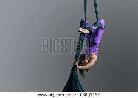 Sporty woman doing exercise with elastics aerial silk ribbons