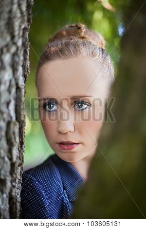 Young Woman Peering Through Tree Trunks