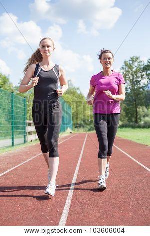 Smiling Friends Jogging On Track Together