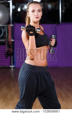 Cute fitness woman wearing in black top and breeches posing with dumbbells and looking at camera on the sport equipment background in the gym waist up