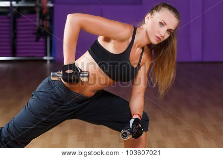 Young pretty woman wearing in black top and breeches posing with dumbbells and looking at camera on the sport equipment background in the gym waist up