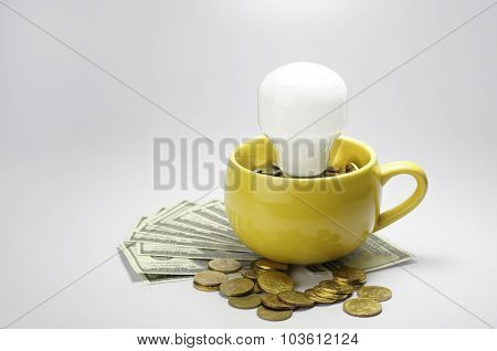 Lightbulb And Cup Full With Money - Finance Concept