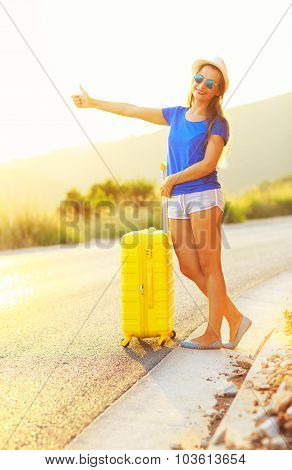 An Attractive Woman With A Yellow Suitcase Is Traveling On The Road Hitchhiking