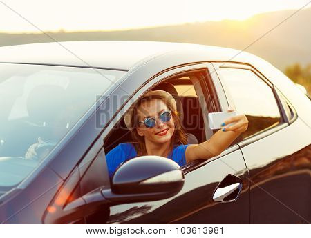 Young Woman In Hat And Sunglasses Making Self Portrait Sitting In The Car