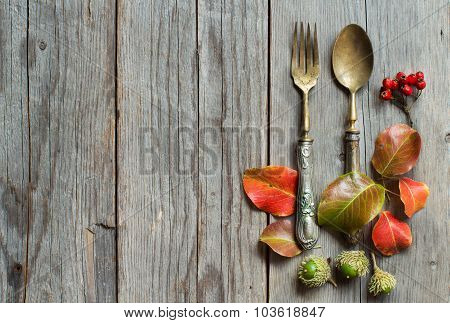 Vintage Fork And Knife With Autumn Leaves On Wood