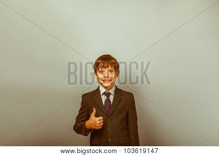 a boy of twelve European appearance in a suit pakazyvaet thumbs