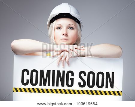 Worker Holding Coming Soon Sign On Information Board