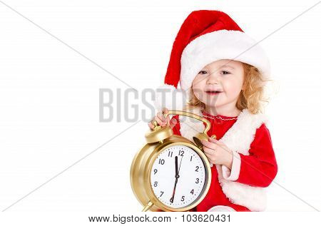 Happy little girl in Santa hat holding a clock in his hands.