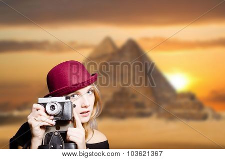 Girl in glasses with retro camera on Egypt pyramid background.