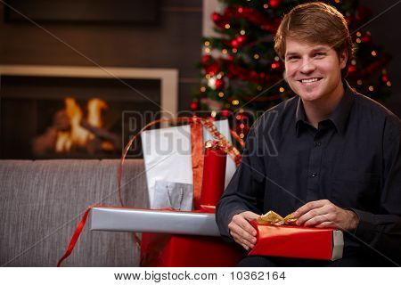 Young Man Wrapping Gifts At Christmas