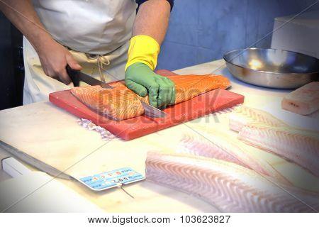 man cutting fresh fish in a supermarket