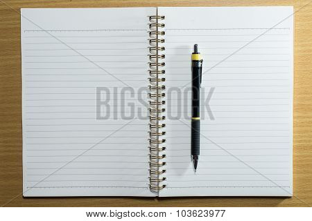 Pen,pencil And Book On Wooden Table. Top View