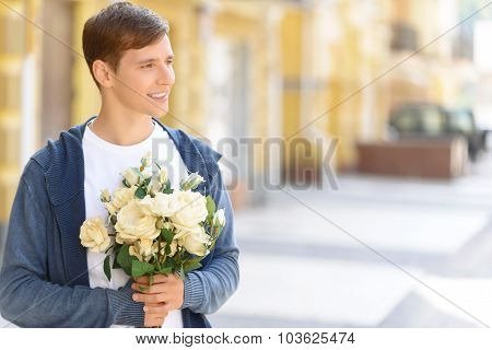 Handsome guy holding flowers