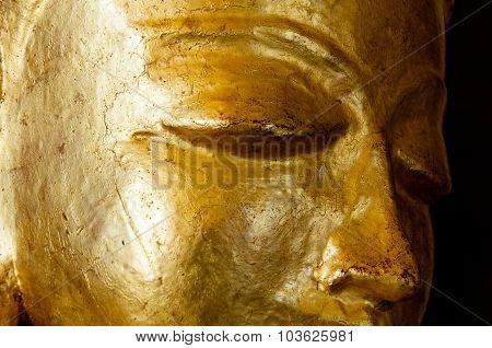 Buddha face gold statue close-up