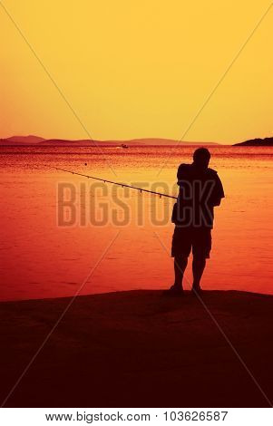 Silhouette Of A Fisherman Standing By The Sea With Sunset, Croatia