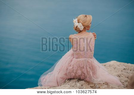 Bride in wedding dress stands on a cliff with a beautiful sea view from the top