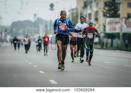 elderly runner in lead at head group of runners