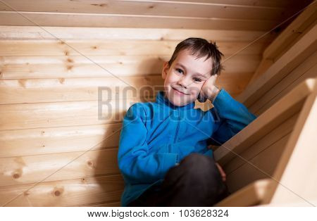 boy sits on a steep wooden staircase
