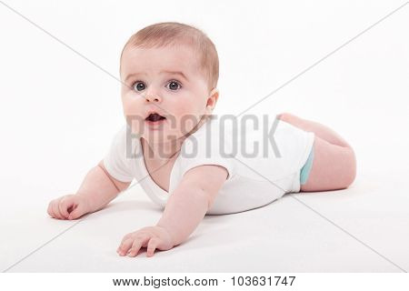Baby In The Body Lying On His Stomach On A White Background And Looking At The Camera