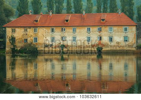 Old ruined rusty castle on the Mreznica river in Duga Resa, Croatia, reflection on water