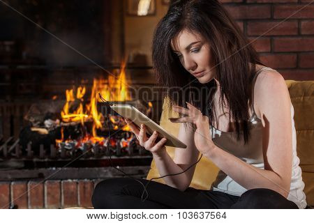 Woman Using Digital Tablet By Fireplace