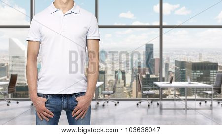 A Man In A White Polo Shirt And Denims Holds His Hands In Pockets. A Modern Panoramic Office Space I
