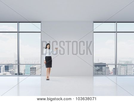 Full Length Brunette Girl In A Formal Clothes Is Pointing Out Something By Her Hand On The White Wal