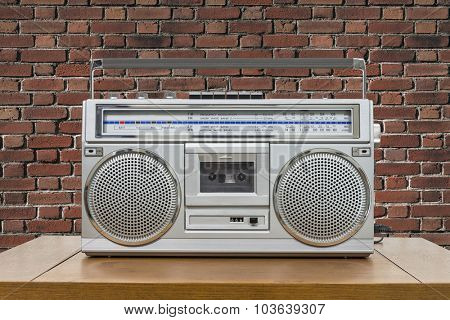 Vintage boombox on wood table with red brick wall.