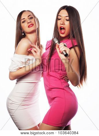 Two sensual girls singing with microphone, isolated on white
