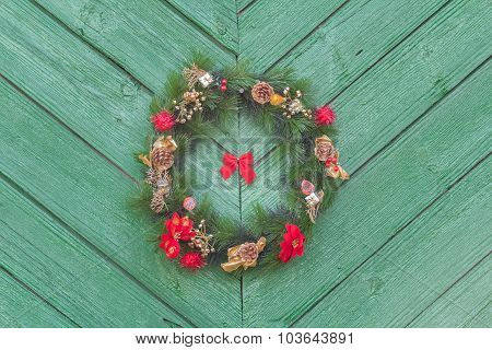 Outdoor X-mas Wreath From Fir Branches At Old Rustic Door Background