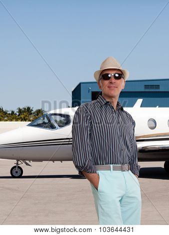 Handsome man standing outside a private jet