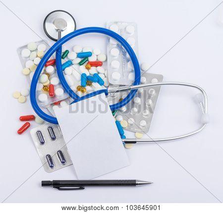 Stethoscope, blank sheet, paper, tablet, pen in a heap
