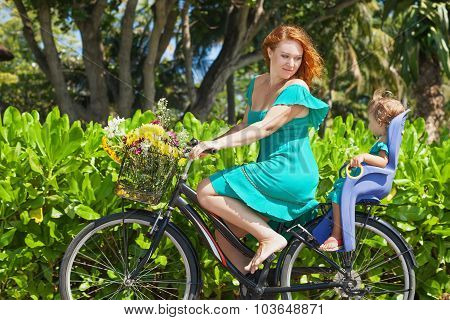 Mother And Daughter Bicycling Along The Sea Sand Beach