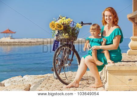 Mother And Daughter With Bicycle On The Sea Beach
