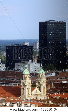 ZAGREB, CROATIA - MAY 31: Basilica of the Sacred Heart of Jesus and the new metal and black glass office buildings in the center of the city in the background in Zagreb, Croatia on May 31, 2015