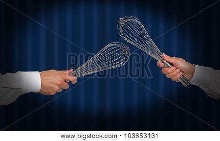 Hands holding whisks under a spot light