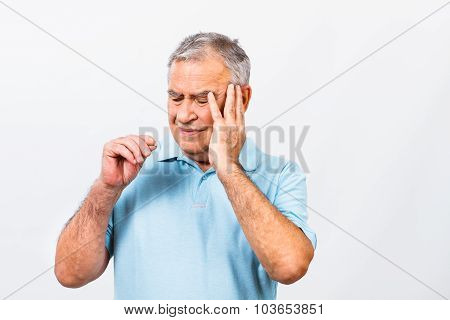 Senior man taking pills for headache