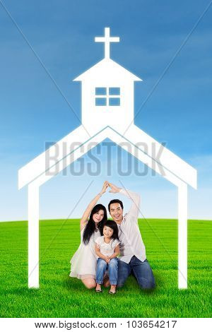Happy Family Sitting Under Church Symbol