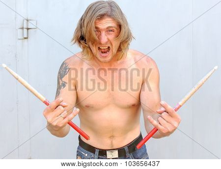 Drummer having fun screams with drumstick