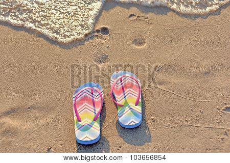 flip flops and footprint on beach
