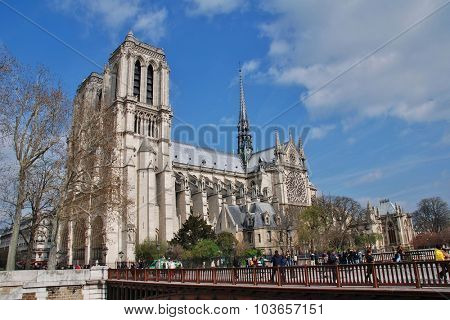 PARIS, FRANCE - MARCH 18, 2014: People walk across the Pont au Double in front of the historic Notre Dame cathedral. Started in 1120, the Catholic cathedral was completed in 1345.