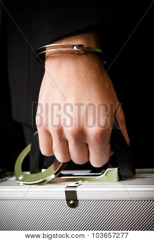 Hand In Handcuffs Holding Money Suitcase