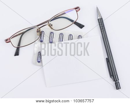 Glasses and tablets. White sheet with a ballpoint pen