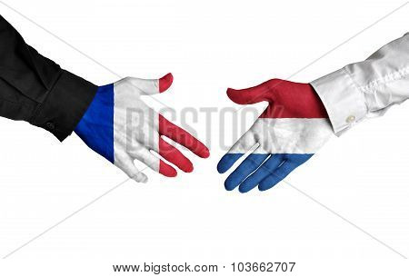 France and Netherlands leaders shaking hands on a deal agreement