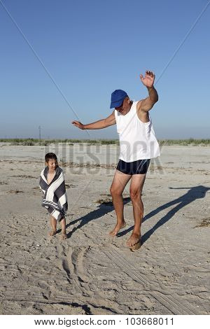 Grandfather With Grandson On A Sand