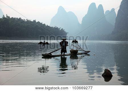 YANGSHUO - JUNE 18: Chinese man fishing with cormorants birds in Yangshuo Guangxi region traditional
